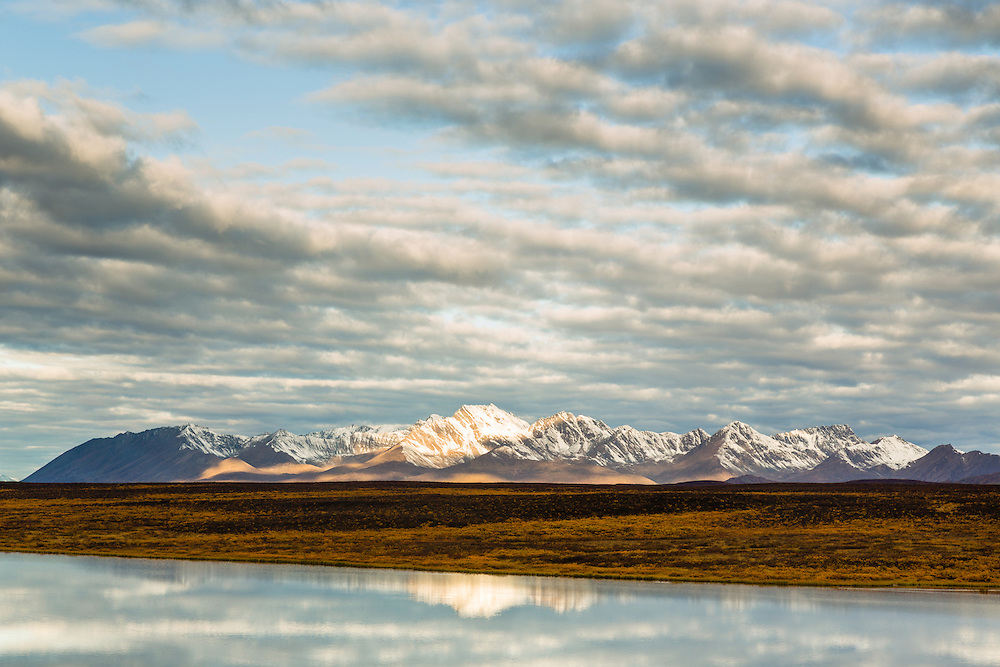 Reflection of the Clearwater Mountains of the Alaska Range on Waterfowel Lakes at sunrise along the Denali Highway in Southcentral Alaska. Autumn.
