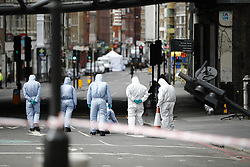 © Licensed to London News Pictures. 05/06/2017. London, UK. Police and forensic officers investigate the scene after a terror attack that killed 7 people on London Bridge and at Borough Market in central London. Photo credit: Tolga Akmen/LNP