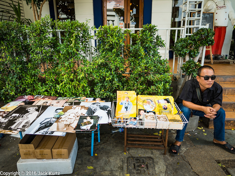 15 OCTOBER 2016 - BANGKOK, THAILAND:  A vendor sells portraits of Bhumibol Adulyadej, the King of Thailand, near the Grand Palace in Bangkok. King Bhumibol Adulyadej died Oct. 13, 2016. He was 88. His death comes after a period of failing health. With the king's death, the world's longest-reigning monarch is Queen Elizabeth II, who ascended to the British throne in 1952. Bhumibol Adulyadej, was born in Cambridge, MA, on 5 December 1927. He was the ninth monarch of Thailand from the Chakri Dynasty and is known as Rama IX. He became King on June 9, 1946 and served as King of Thailand for 70 years, 126 days. He was, at the time of his death, the world's longest-serving head of state and the longest-reigning monarch in Thai history.     PHOTO BY JACK KURTZ