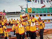 "23 JUNE 2015 - MAHACHAI, SAMUT SAKHON, THAILAND: Men carry offerings for City Pillar off a fishing boat during the procession in Mahachai. The Chaopho Lak Mueang Procession (City Pillar Shrine Procession) is a religious festival that takes place in June in front of city hall in Mahachai. The ""Chaopho Lak Mueang"" is  placed on a fishing boat and taken across the Tha Chin River from Talat Maha Chai to Tha Chalom in the area of Wat Suwannaram and then paraded through the community before returning to the temple in Mahachai.  PHOTO BY JACK KURTZ"