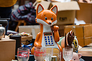 An orange fox calculator, raising a paw, at To-ji Temple flea market in Kyoto, Japan.