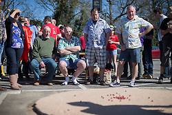 © Licensed to London News Pictures. 25/03/2016. Crawley, UK. Team members watch as a player takes a shot in the World Marbles Championships in the car park of the Greyhound pub in Tinsley Green near Crawley. The competition has taken place every year since 1932 with teams from the USA, Algeria, Australia and Europe taking part. Photo credit: Peter Macdiarmid/LNP