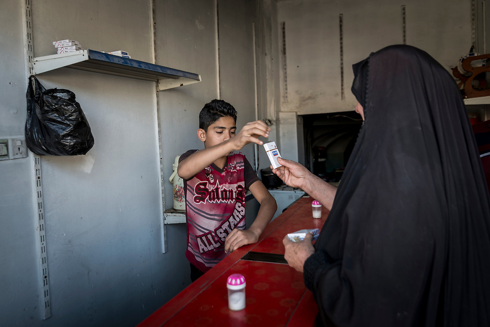 A woman buys cigarettes from a small shop that's recently reopened in Mosul's Old City.