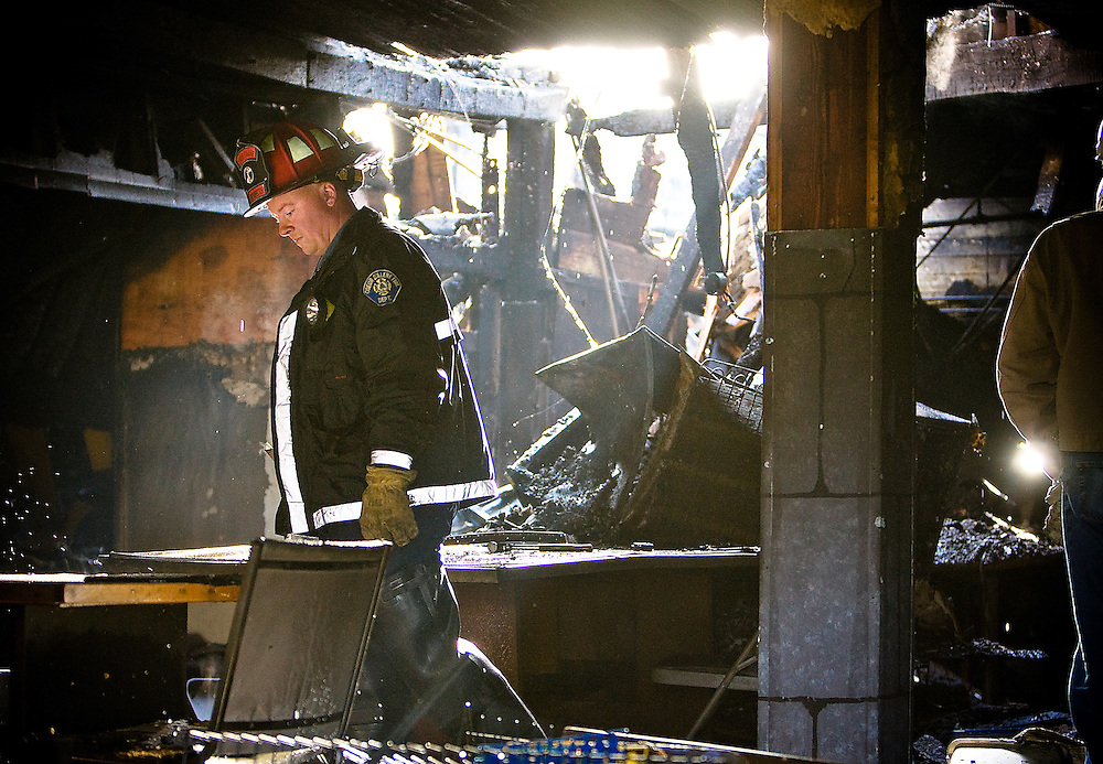 JEROME A. POLLOS/Press..Coeur d'Alene Fire Inspector Brian Halvorson walks through the rubble Monday left inside of Gamer's Haven on the corner of Sherman Avenue and 12th Street. A fire Sunday night destroyed three business and left a number of people homeless.