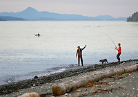 A young fisherman hooks into a migrating Salmon swimming along the shores of the Cluxewe Resort, just north of Port McNeill.  Cluxewe Resort, Northern Vancouver Island, British Columbia, Canada.