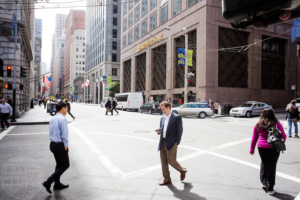 Zakenmensen lopen al bellend en sms-end door de financial district in San Francisco. De Financial District in San Francisco waar veel hoofdkantoren van banken en grote ondernemingen zijn gevestigd. De Amerikaanse stad San Francisco aan de westkust is een van de grootste steden in Amerika en kenmerkt zich door de steile heuvels in de stad.<br /> <br /> Business man at the Financial District of San Francisco where headquarters of banks and financial companies are located. The US city of San Francisco on the west coast is one of the largest cities in America and is characterized by the steep hills in the city.