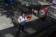 As the UK's Coronavirus death toll during the government's social distancing lockdown, rose by 384 to 33,998, and the R rate of infection is reported to be between 0.7 and 1.0, a man speaking on his phone stands at a bus stop while wearing plastic gloves, on 15th May 2020, in London, England.