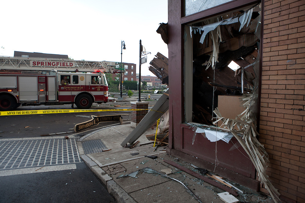 Firefighters drive past damaged buildings on Main St in downtown Springfield, MA where a tornado struck on Wednesday afternoon June 1, 2011.  (Matthew Cavanaugh for The Boston Globe)