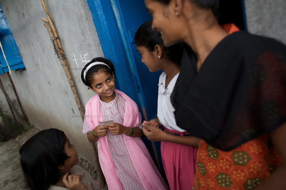 At home, Vasanti smiles to daughter Shruda, 10. Both are HIV positive. Vasanti Shinde, 26, works for the Save Foundation. <br />