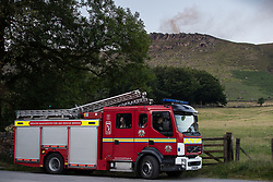 "© Licensed to London News Pictures . 28/06/2018 . Saddleworth , UK . A fire engine by Dove Stone reservoir as the army are being called in to support fire-fighters , who continue to work to contain large wildfires spreading across Saddleworth Moor and affecting people across Manchester and surrounding towns . Very high temperatures , winds and dry peat are hampering efforts to contain the fire , described as "" unprecedented "" by police and reported to be the largest in living memory . Photo credit: Joel Goodman/LNP"