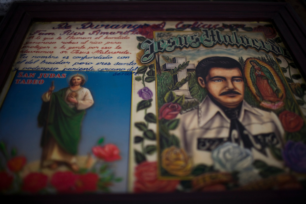 A picture of Jesus Malverde and Jesus Christ hangs in Culiacan, Mexico.  Malverde is a folk saint worshipped by many people in the underworld and often associated with narcoculture and drug dealers. He is thought of as the Mexican version of Robin Hood, looking after those who have been forgotten by the Church and are involved in a life of crime.  People come to the chapel to show their respect and pray.