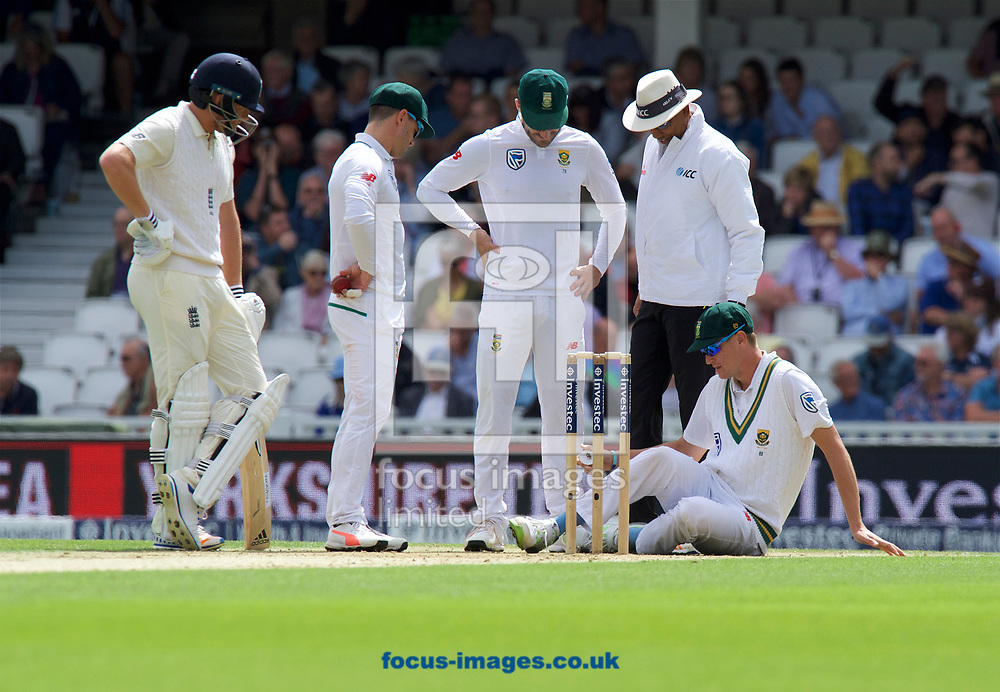Bowler Chris Morris of South Africa cleans his studs before bowling. Watched by Jonny Bairstow of England and Umpire Aleem Dar during the 100th Investec Test Match match at the Kia Oval, London<br /> Picture by Alan Stanford/Focus Images Ltd +44 7915 056117<br /> 28/07/2017