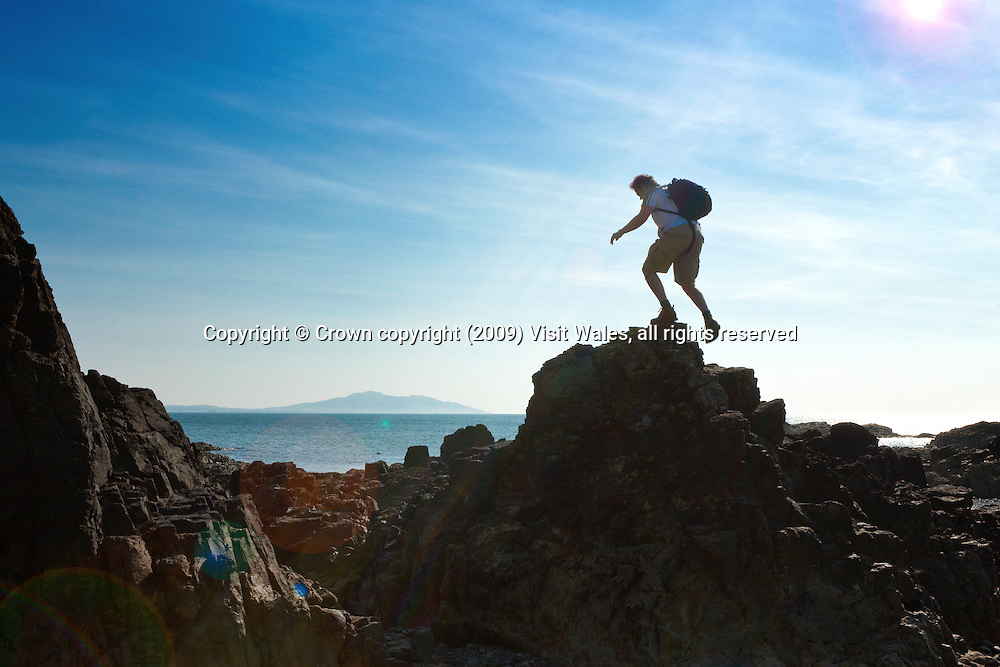 Young man climbing coastal rocks (with Holyhead Mountain to background)<br /> Church Bay<br /> Anglesey<br /> North<br /> Walking<br /> Activities &amp; Sports
