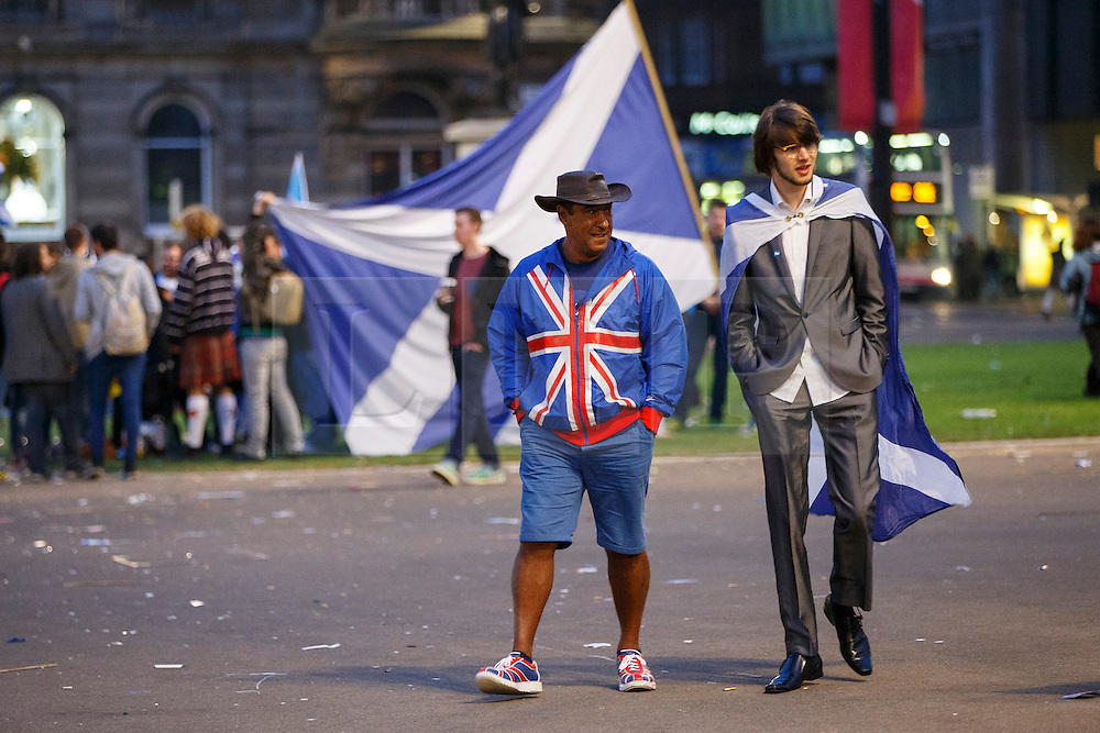 © Licensed to London News Pictures. 19/09/2014. Glasgow, UK. A union supporter walking amongst disappointed 'Yes' voters and campaigners as Scotland decides to stay in the union, at George Square in Glasgow on Friday, 19 September 2014, after the Scottish independence referendum. Photo credit : Tolga Akmen/LNP