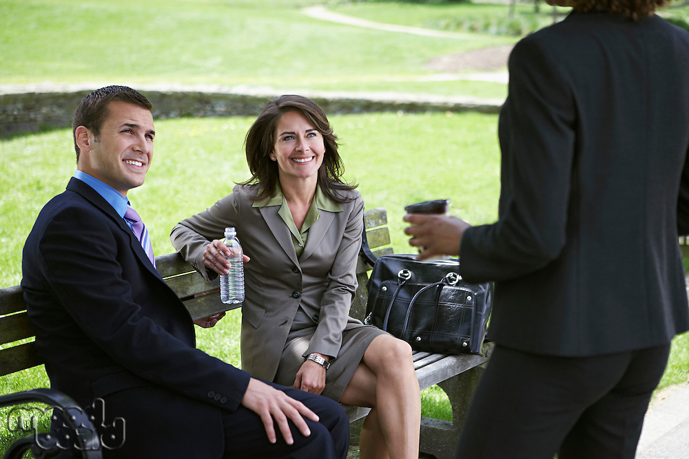 Business man and woman sitting on park bench looking at colleague
