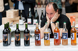 © Licensed to London News Pictures. 16/05/2016. London, UK. A wine seller takes a rest during a hectic afternoon of selling.  Buyers and wine lovers visit the Raw Wine Fair at the Old Truman Brewery near Brick Lane.  The fair brings over 180 artisan growers and wine makers from around the world who specialise in producing organic, biodynamic and naturally made wines with minimal additives. Photo credit : Stephen Chung/LNP