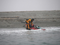 A kayaker preparing to enter the kayak on Spitzbergen