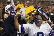 IRVING, TX - NOVEMBER 29: Two Dallas Cowboys fans with team colored painted faces and a blue cheese-head have fun pretending to beat up on a Green Bay Packers fan with a yellow cheese-head during the game on November 29, 2007 at Texas Stadium in Irving, Texas. The Cowboys defeated the Packers 37-27. ©Paul Anthony Spinelli