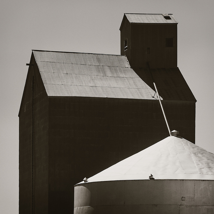 A massive old grain elevator stands silently next to a huge grain storage tank.