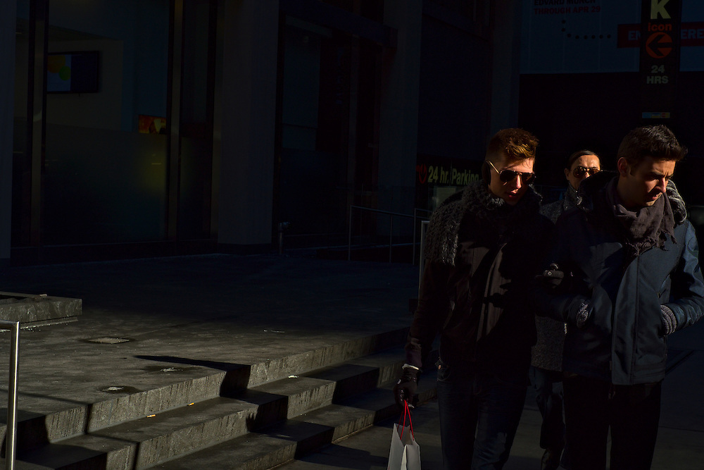 Men looking to side while walking in winter afternoon sun