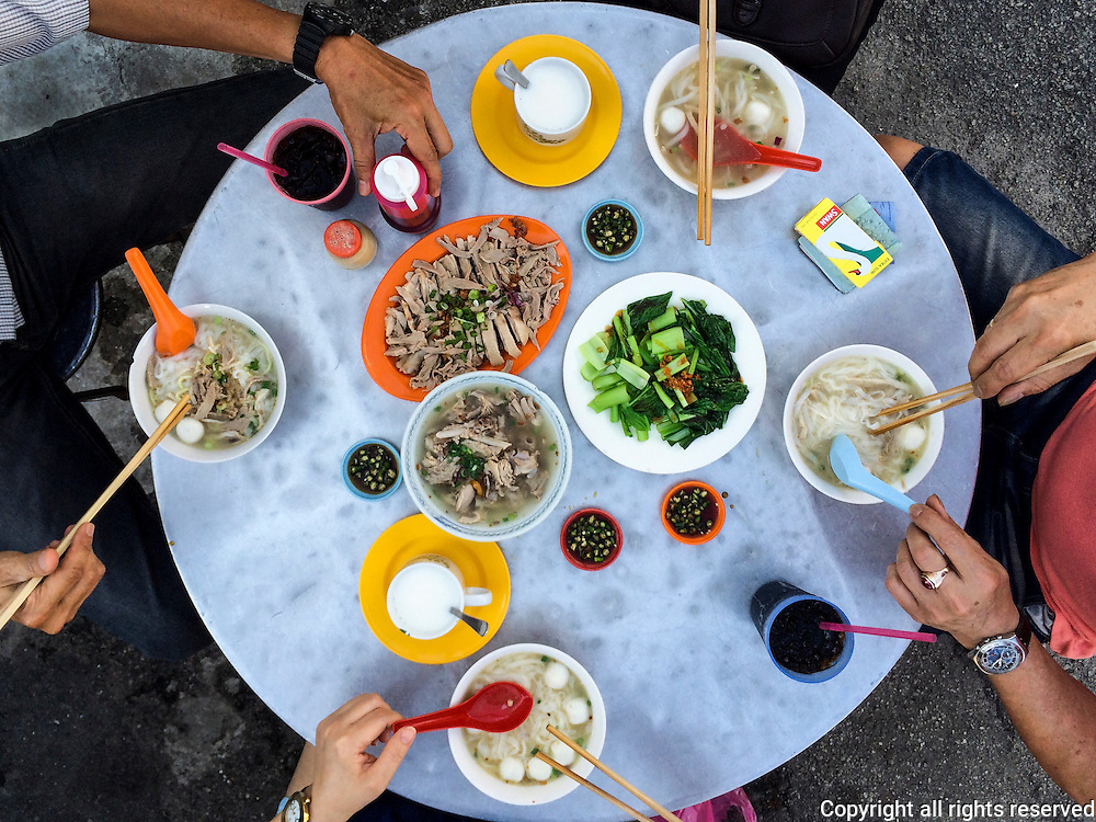 Tourists breakfast at a street food stall in George Town, Penang, Malaysia. Koay teow th'ng (rice noodles in a savory soup), accompanied by gai lan, shredded duck, soup with duck parts and hot chilies served in soy sauce.
