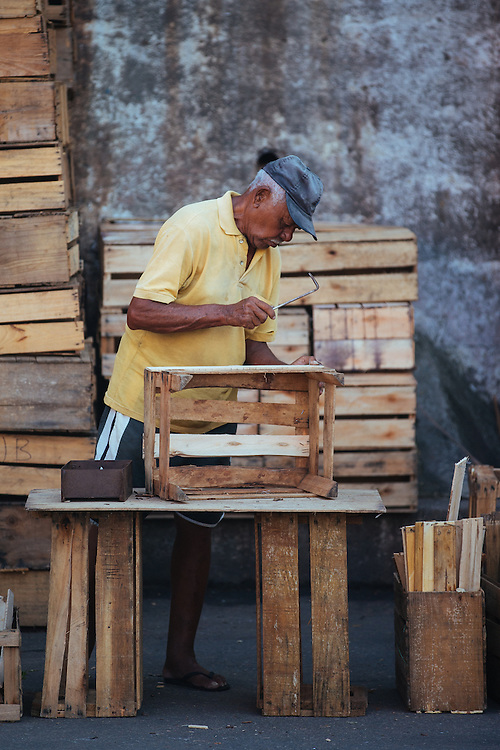 A man assembles crates for fruit and veg outside Rio's CADEG Market.