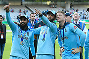 Adil Rashid of England, Moeen Ali of England with Jos Buttler of England look up to the players family balcony after winning the Cricket World Cup on the lap of honour during the ICC Cricket World Cup 2019 Final match between New Zealand and England at Lord's Cricket Ground, St John's Wood, United Kingdom on 14 July 2019.