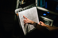 """ROME, ITALY - 27 JUNE 2017: Assistant director Martina Santese checks the Don Giovanni score during the performance of """"Don Giovanni OperaCamion"""", an open-air opera performed on a truck in San Basilio, a suburb in Rome, Italy, on June 27th 2017.<br /> <br /> Director Fabio Cherstich's idae of an """"opera truck"""" was conceived as a way of bringing the musical theatre to a new, mixed, non elitist public, and have it perceived as a moment of cultural sharing, intelligent entertainment and no longer as an inaccessible and costly event. The truck becomes a stage that goes from square to square with its orchestra and its company of singers in Rome. <br /> <br /> """"Don Giovanni Opera Camion"""", after """"Don Giovanni"""" by Wolfgang Amadeus Mozart is a new production by the Teatro dell'Opera di Roma, conceived and directed by Fabio Cherstich. Set, videos and costumes by Gianluigi Toccafondo. The Youth Orchestra of the Teatro dell'Opera di Roma is conducted by Carlo Donadio."""