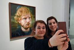 © Licensed to London News Pictures. 03/05/2017. London, UK.  (L to R) Martina Deligia and Ilenia Motta, Ed Sheeran fans from Italy, visit the National Portrait Gallery to take a selfie with a newly acquired portrait of the popular singer-songwriter Ed Sheeran, by artist Colin Davidson.  The 4ft x 4ft painting oil painting is the first portrait painted of the singer since the start of his professional career and has just been put on public display.   Photo credit : Stephen Chung/LNP