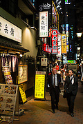 The alleys near Shinjuku station are used by japanese salarymen to have a quick and cheap meal after a day's work. Two work colleagues stroll by after dinner.