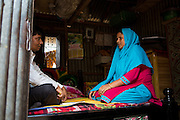 Rahidul Islam (right) interviewing a garment worker called Kohinur (left) in her home in Dhaka, Bangladesh. <br /> <br /> Rahidul works for the BRAC microfinance, financial diaries project. This programme works to improve the financial literacy of garment workers.