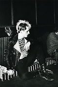 A punk, with a mohican and leather jacket, sat down at a gig, UK, 1980.