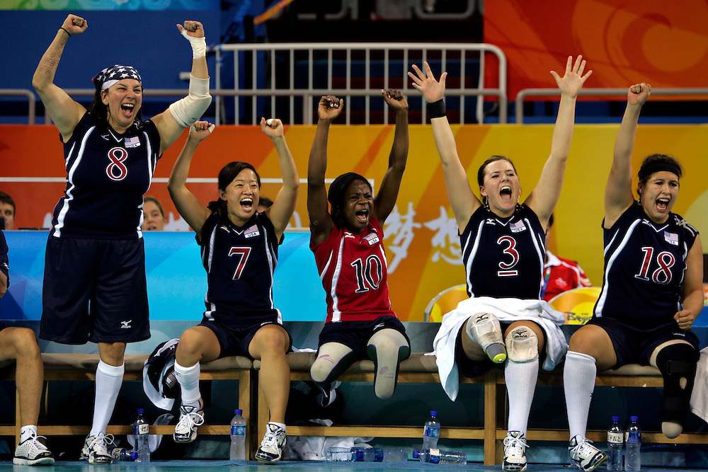 Sugui Kriss, second left, cheers along with her team mates, Hope Lewellen, first left, Kari Miller, center, Brenda Maymon, second right and Alexandra Gouldie, first right, as her American team scores against China during a sitting volleyball match  at the Paralympic games in Beijing , China, Tuesday, Sept.9, 2008. Sugui Kriss always wanted to return to China to find a few of her roots and, perhaps, to leave her mark on the country She's done both She marched into the National Stadium _ the Bird's Nest _ last weekend for the opening ceremony of Beijing's Paralympic Games, representing the U.S. as a member of its sitting volleyball team. How different this was from her early life in southern China; an abandoned infant who was raised in an orphanage in Kunming until she was adopted 13 years ago by the American couple Charles and Marilyn Kriss. If Paralympic organizers are looking for a poster girl, SuGui Kriss would be a perfect choice.