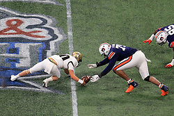UCF Knights quarterback McKenzie Milton (10) and Auburn Tigers defensive lineman Andrew Williams (79) try to recover a fumble during the 2018 Chick-fil-A Peach Bowl NCAA football game on Monday, January 1, 2018 in Atlanta. (Daniel Shirey / Abell Images for the Chick-fil-A Peach Bowl)