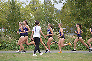 Washington Huskies director of cross country and track and field Maurica Powell (in white) encourages her runners in the women's 3 mile run at the UW/Seattle University Open race at Warren G. Magnuson Park., Friday, Aug. 30, 2019, in Seattle. (Paul Merca/Image of Sport)