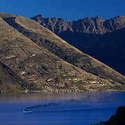The TSS Earnslaw,  a 1912 Edwardian vintage twin screw steamer on the waters of Lake Wakatipu in, Queenstown, New Zealand. .It is one of the oldest tourist attractions in Central Otago, and the only remaining passenger-carrying coal-fired steamship in the southern hemisphere..The TSS Earnslaw heads along Lake Wakatipu from Queenstown  daily, running tourist trips to Walter Peak Station passing magnificent  peaks and contrasting shoreline foliage along the lakeside. Queenstown, New Zealand. 28th April 2011. Photo Tim Clayton