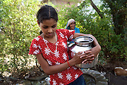 . Pooja, 14, a student from the village of Pathpuri, Hoshangabad, Madhya Pradesh, India, taking part to the children's journal, a project launched by Dalit Sangh, an NGO which has been working for the uplift of scheduled castes for the past 22 years, is collecting water on a village road. Dalit Sangh is working in collaboration with Unicef India to promote education and awareness within backward communities.