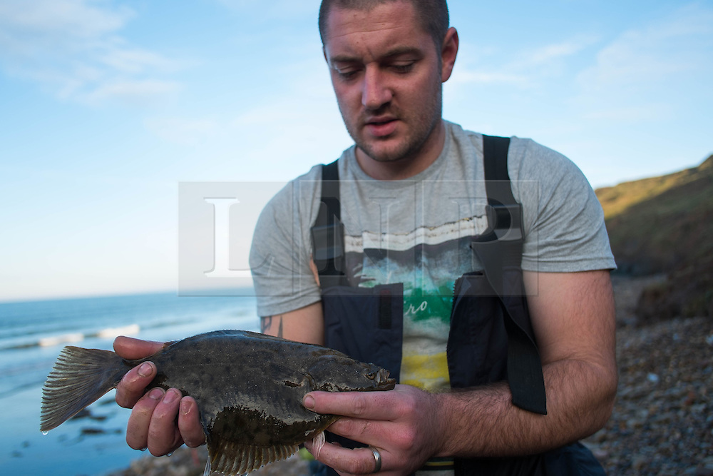 © Licensed to London News Pictures. <br /> 12/10/2014. <br /> <br /> Saltburn, United Kingdom<br /> <br /> David Ward from Guisborough poses with his catch, a flatty, during the annual Jim Maidens memorial beach fishing competition in Saltburn by the Sea in Cleveland. <br /> The competition is held each year to mark the death of Saltburn plumber and keen fisherman Jim Maidens who died in 1998 when he was killed after being swept overboard from his boat 'Corina' close to the beach at Saltburn.<br /> <br /> Photo credit : Ian Forsyth/LNP