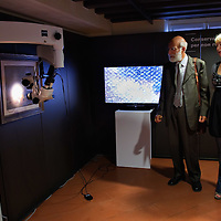 """VENICE, ITALY - SEPTEMBER 10: Professor Giuseppe Basile (L)and Curator Mariella Gnani (R) check a new microscope system to inspect paintings in detailsduring the press opening of  """"Dalla Figura Alla Figurazione Nel '900 Italiano"""" on September 10, 2011 in Venice, Italy. The exhibition """"Dalla Figura Alla Figurazione Nel '900 Italiano"""" at Palazzo Loredan shows for the very first time the important collection owned by Giuseppe Merlini."""