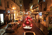 Cars lined up along a narrow Parisian street at night. Paris, France