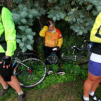 Mike Meyer finds shelter from the rain under a tree Thursday afternoon during the fifth day of the Tour de Kota.