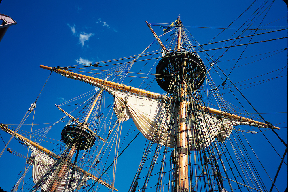 The mast of an old sailboat against a blue sky