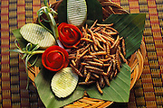 "Fried bamboo larva on a banana leaf with tomato roses, scalloped cucumbers and spring onions. In Thai the larvae are called rot duan, ""express train,"" because they resemble tiny trains. They taste ""like salty crispy shrimp puffs"" says Peter Menzel. In the Kan Ron Ban Suan Restaurant, Chiang Mai, Thailand. Image from the book project Man Eating Bugs: The Art and Science of Eating Insects."
