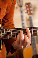 Close-up of mid adult man's fingers while playing guitar