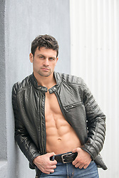 shirtless muscular man in a leather jacket