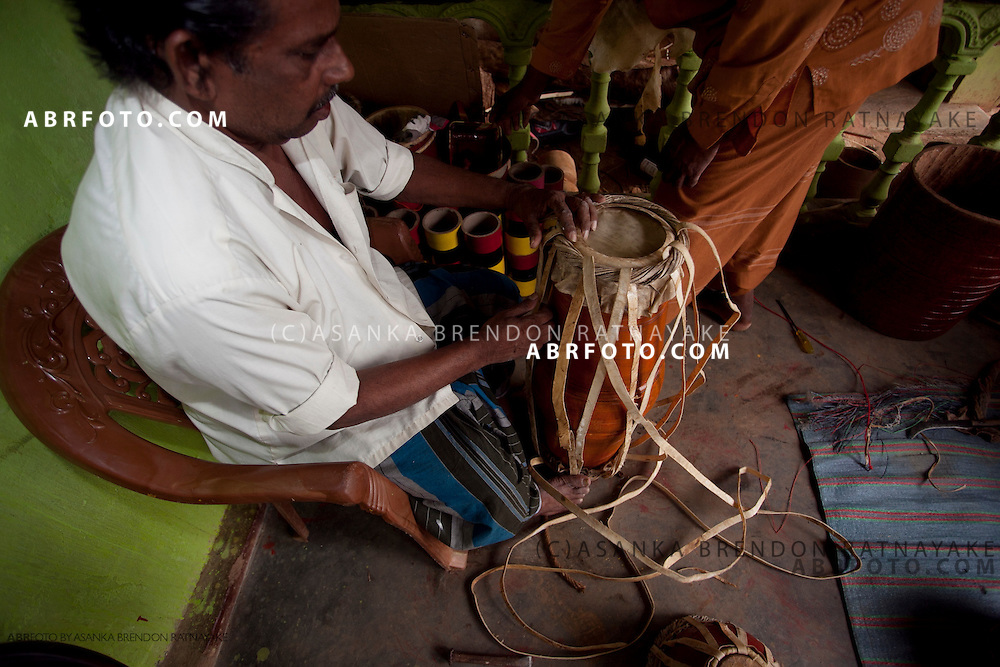 A drum craftsmen straps & tightens the drum with leather straps.