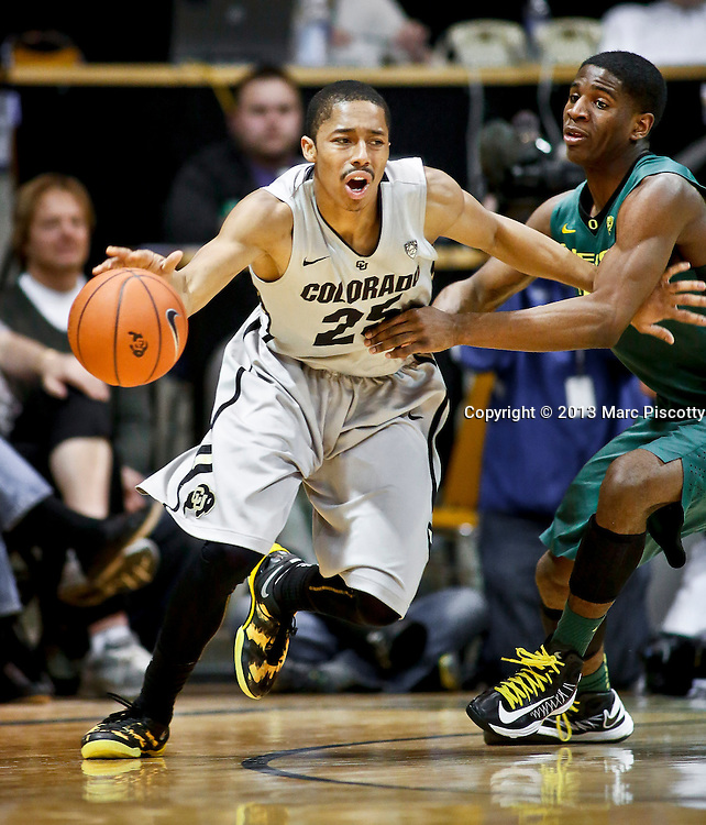 SHOT 3/7/13 8:24:04 PM - Colorado's Spencer Dinwiddie #25 tries to drive past Oregon's Damyean Dotson #21 during their Pac-12 Conference regular season basketball game at the Coors Events Center on the University of Colorado campus in Boulder, Co. Colorado won the game 76-53..(Photo by Marc Piscotty / © 2013)