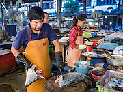 30 DECEMBER 2015 - BANGKOK, THAILAND:  A fish monger cuts up a fish in Bang Chak Market. The market is supposed to close permanently on Dec 31, 2015. The Bang Chak Market serves the community around Sois 91-97 on Sukhumvit Road in the Bangkok suburbs. About half of the market has been torn down. Bangkok city authorities put up notices in late November that the market would be closed by January 1, 2016 and redevelopment would start shortly after that. Market vendors said condominiums are being built on the land.           PHOTO BY JACK KURTZ