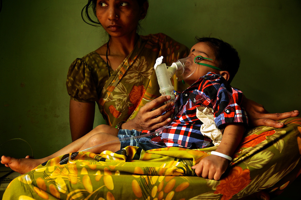 A mother assisting her baby breathing in a slum in Mumbai, one of the largest concentration of low income households in the world. Every day hundreds of millions of people in India wake up at dawn and work hard until sunset to find their way out of poverty. Many of these people cannot access clean water and electricity, nor pay school fees for their children or see a doctor when they are sick. Their basic needs have been largely unmet, neither by public services nor by the market that doesn't consider them as potential customers. Access to health care services in India by low-income people is limited due to the poor supply from the public service, especially in remote areas such as slums. Every day hundreds of millions of people in India wake up at dawn and work hard until sunset to find their way out of poverty. Many of these people cannot access clean water and electricity, nor pay school fees for their children or see a doctor when they are sick. Their basic needs have been largely unmet, neither by public services nor by the market that doesn't consider them as potential customers. Access to health care services in India by low-income people is limited due to the poor supply from the public service, especially in remote areas such as slums.