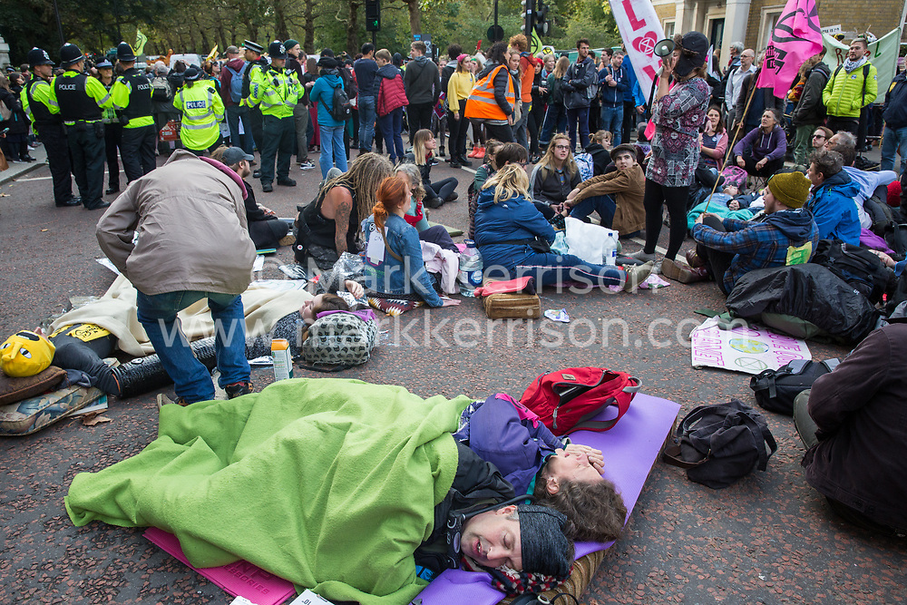 London, UK. 9 October, 2019. Climate activists from Extinction Rebellion use lock-on arm tubes to block Birdcage Walk on the third day of International Rebellion protests to demand a government declaration of a climate and ecological emergency, a commitment to halting biodiversity loss and net zero carbon emissions by 2025 and for the government to create and be led by the decisions of a Citizens' Assembly on climate and ecological justice.